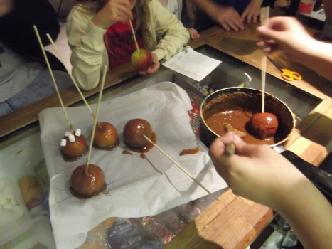 Dipping the apples in the hot toffee mix, in groups of three at a time